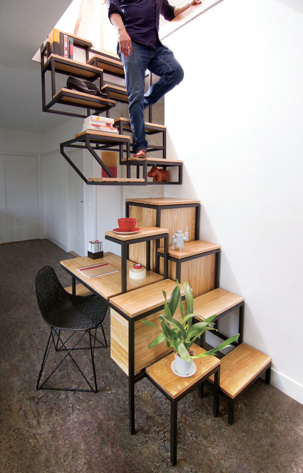 A man is walking down the Mieke Meijer Objet Eleve, a suspended staircase with storage, a desk, and a side table.