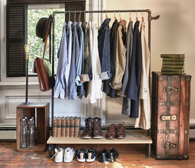 A portable DIY closet made of pipes, a storage crate, a shelf, and a vintage trunk.