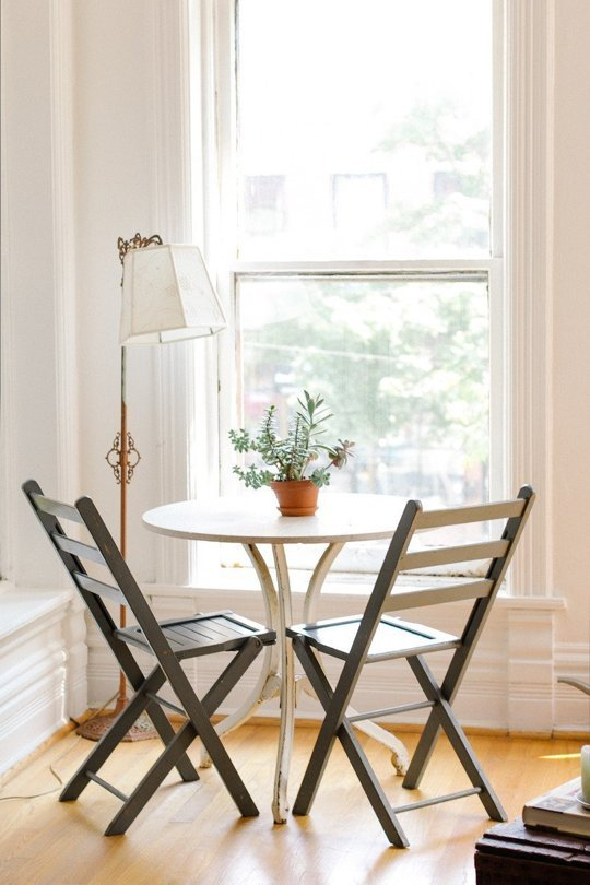 A simple decorating idea to make an apartment look bigger is to use a bistro table as a dining table and desk.