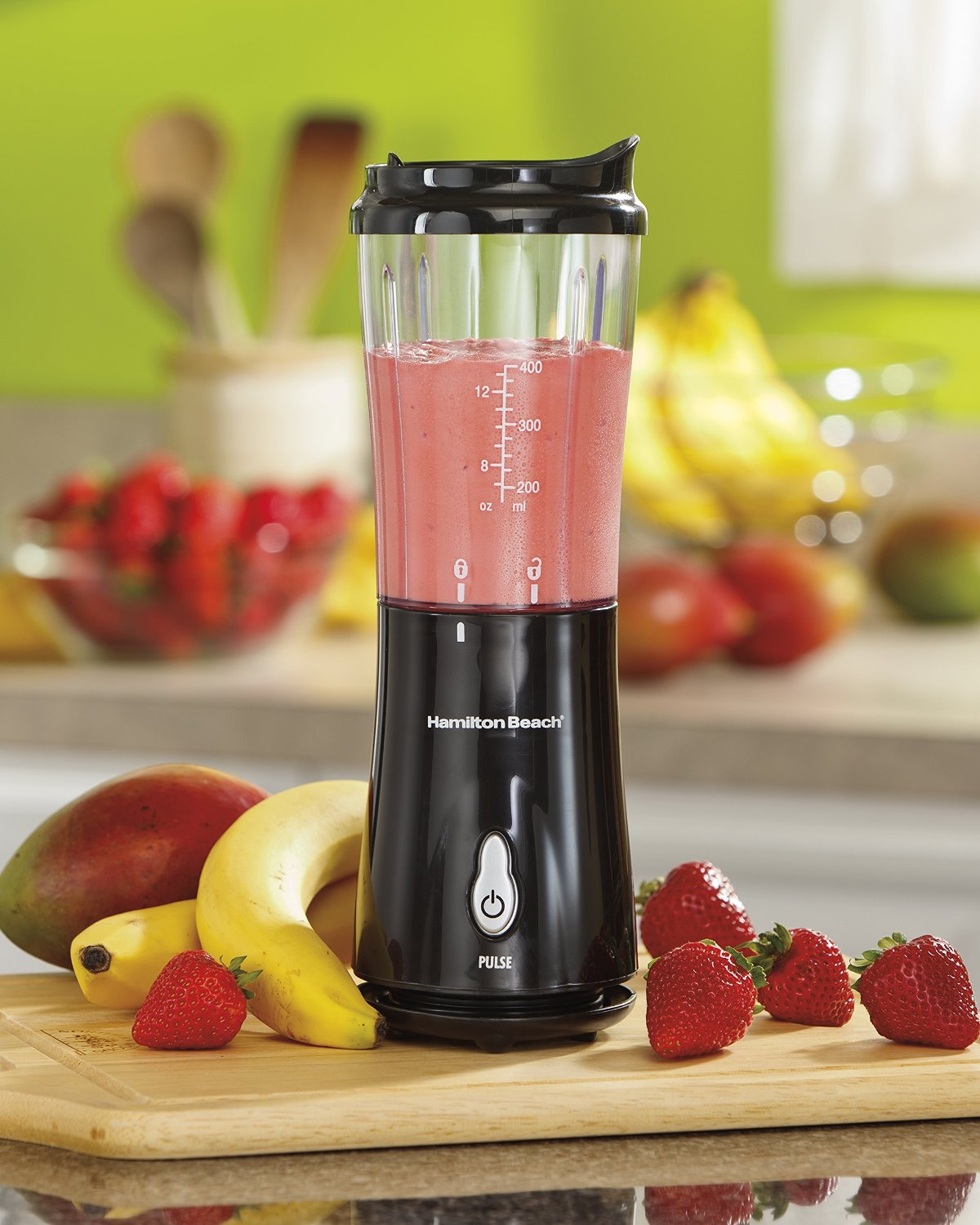 A black Hamilton Beach personal blender next to bananas and strawberries on a kitchen counter.