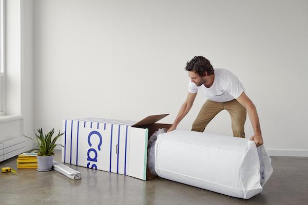A man is unfurling a Casper mattress inside an aparment.
