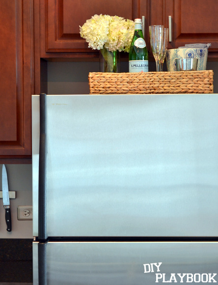 To save space in a small kitchen, put a tray on top for extra storage.