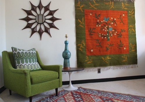 A midcentury living room decorated with a tapestry, chair, side table, area rug.