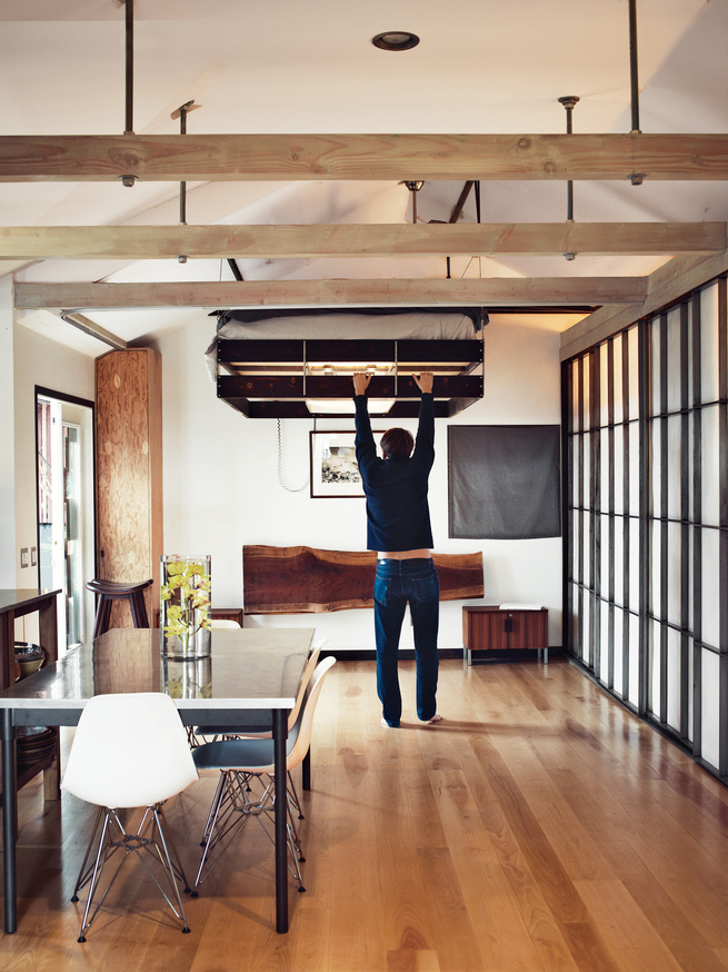 A man is pulling down a bed from the ceiling in a small apartment.