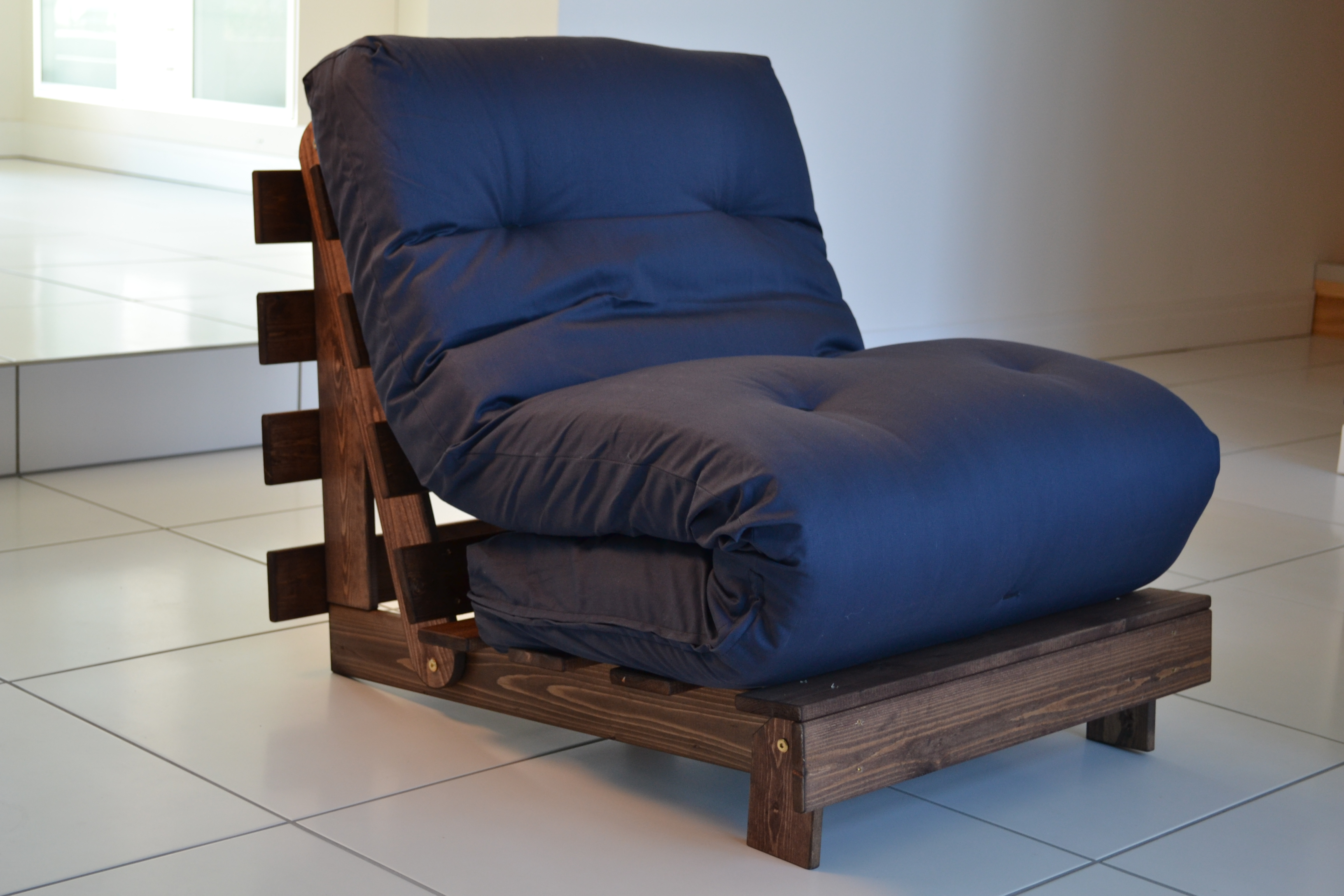 A Blue Futon Folded Up Onto Brown Diy Wood Pallet Chair