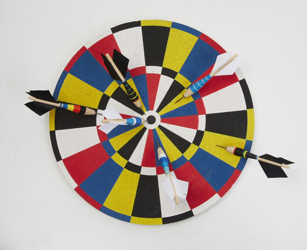 A Fredericks & May dartboard mounted to the wall in a small apartment with multiple darts poking into it.
