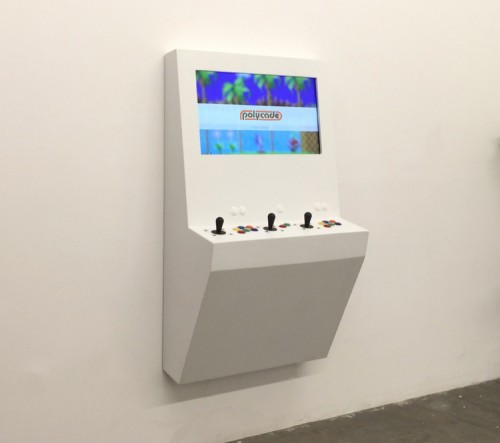 A white Polycade arcade game is mounted to a white wall in a tiny apartment.