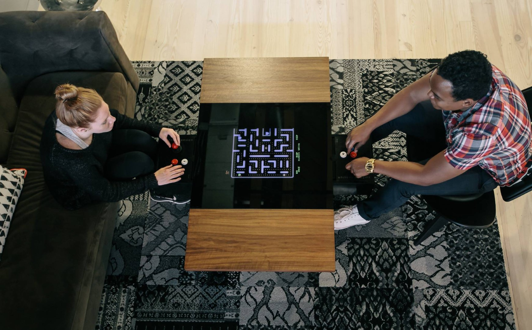 A man and woman playing Surface Tension's Dual Arcade table in a living room.