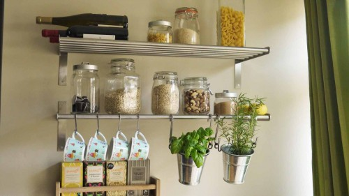 Metal shelves and S hooks used for cheap storage in a small kitchen.
