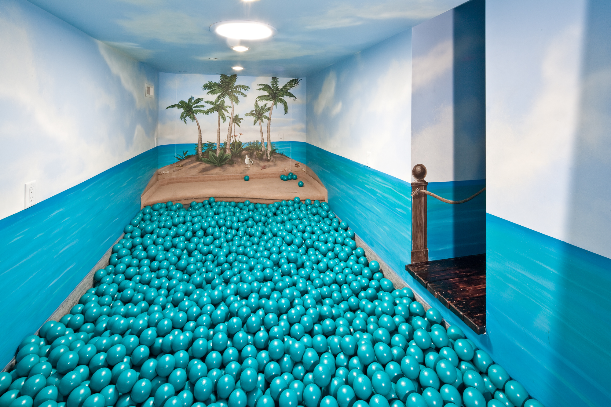 An indoor ball pit that looks like a tropical island on a sunny day with clear skies.
