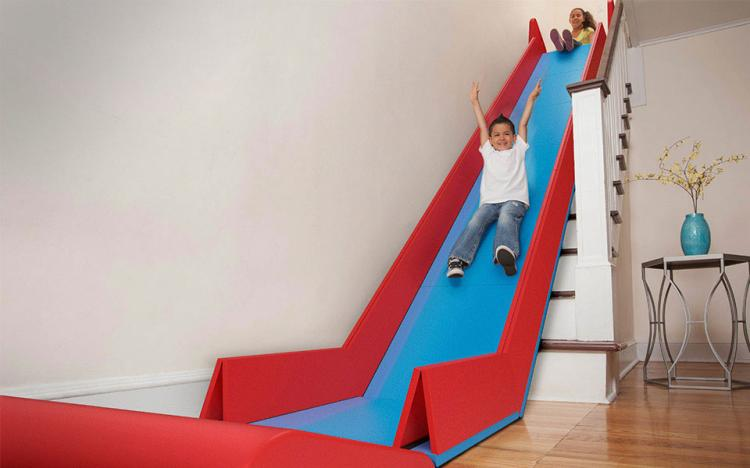 A boy sliding down a Slide Rider, an indoor slide on stairs.