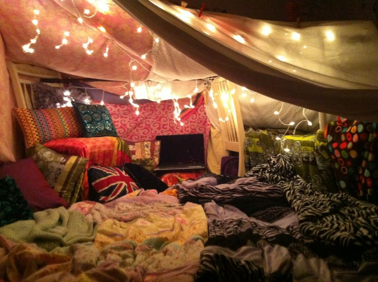 A cozy blanket fort with pillows, string lights, and a laptop.
