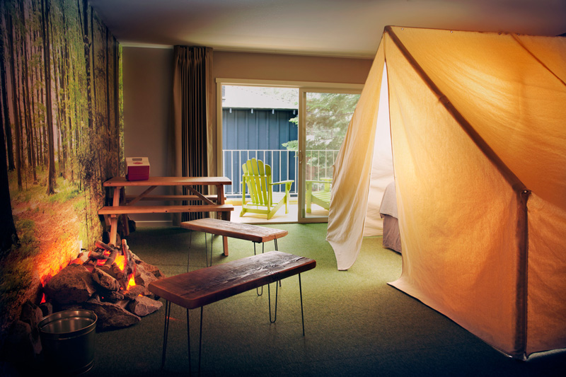 Camp indoors at Basecamp Hotel, which includes a tent, picnic table, benches, an indoor fire pit, and more.