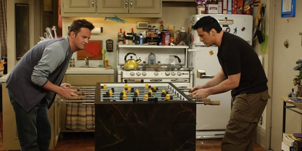 Chandler and Joey from Friends are playing foosball in their apartment that's located in Greenwich Village, Manhattan.