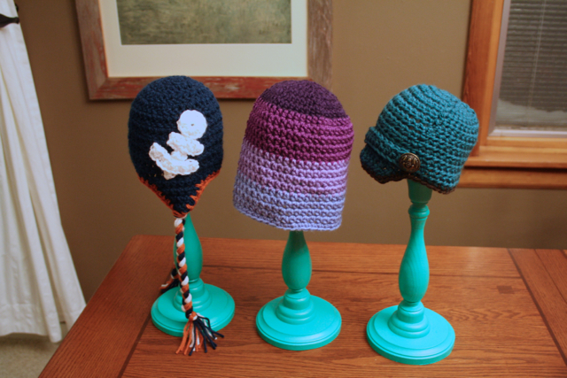 DIY storage for small spaces: winter hats on candlesticks.