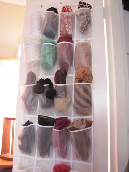 over-the-door shoe organizer storing winter gloves, scarves, and hats