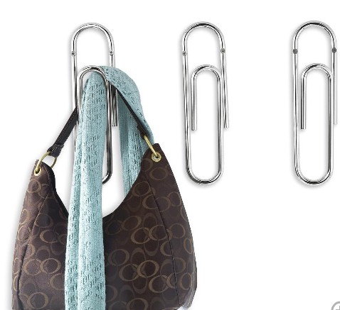 Easy storage ideas: giant paper clips storing a designer bag and scarf.
