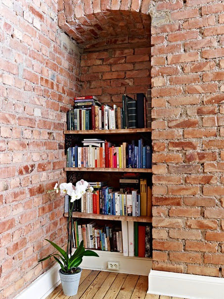 A DIY bookcase in a tiny apartment's exposed brick nook is a prime example of a cool book storage hack.