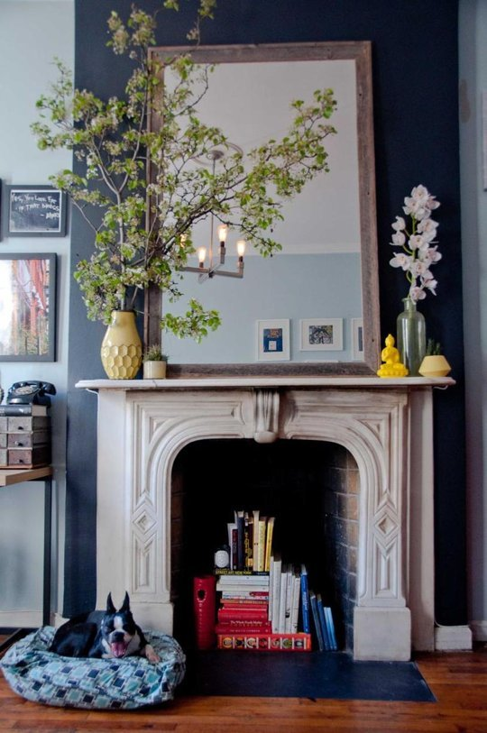 A fireplace used as an easy book storage hack in a 250 sq ft tiny apartment in NYC.