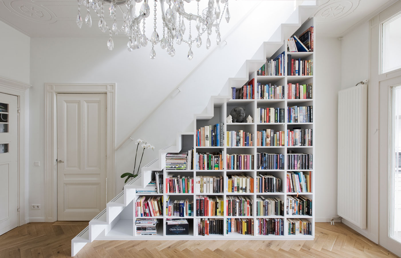 A DIY bookcase in a staircase is one of many creative book storage hacks for small apartments.