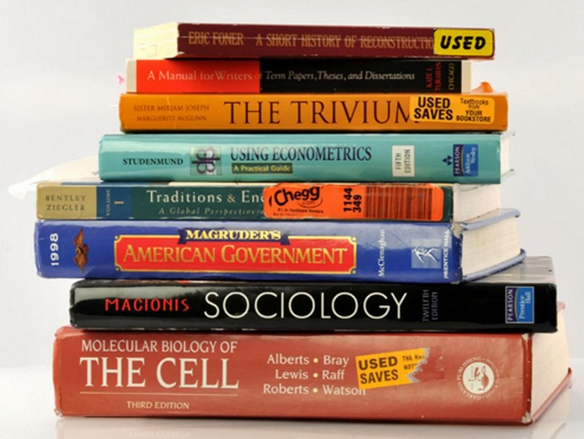 A stack of used college textbooks including Molecular Biology of the Cell, Macionis Sociology, Macgruder's American Government, and more.