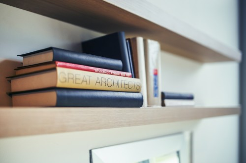 An organized wooden floating bookshelf is storing 11 different books.