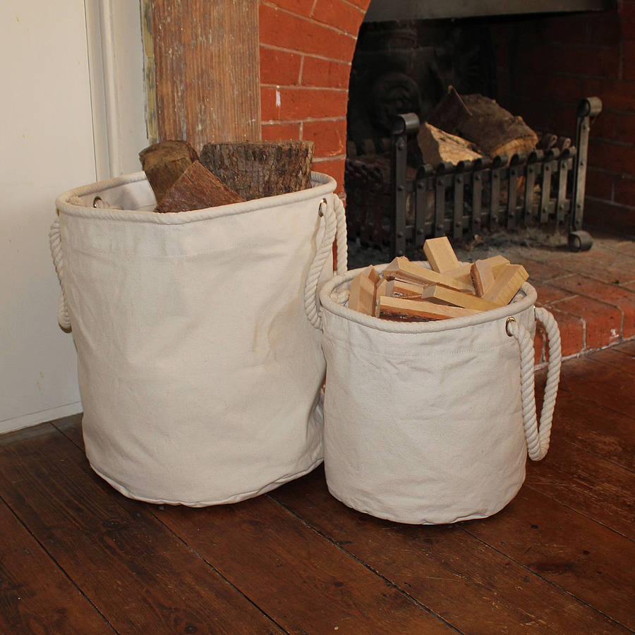 A large and small canvas storage baskets are storing logs and kindling in a small apartment with a fireplace.