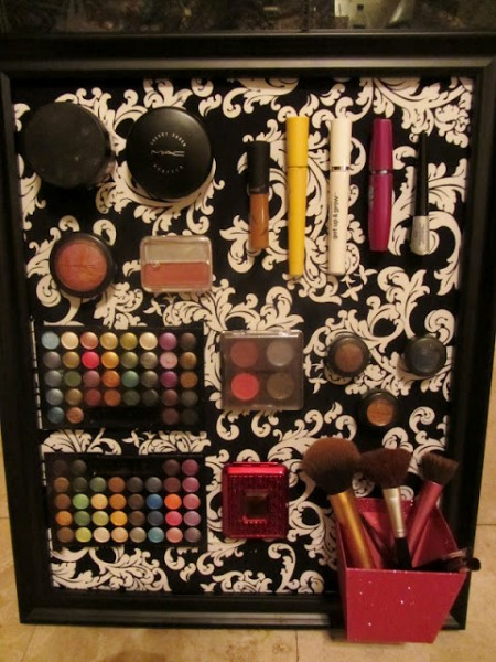 A DIY makeup board is organizing and storing eyeshadow, blush, lip liner, eyeliner, and various makeup brushes.