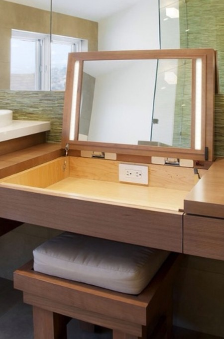 Hidden makeup storage and a mirror with lights is built into a wooden vanity table.