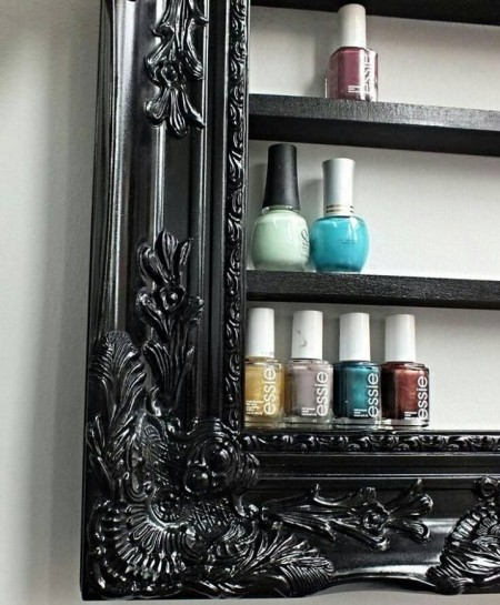 A black DIY picture frame with storage shelves is storing nail polish bottles.
