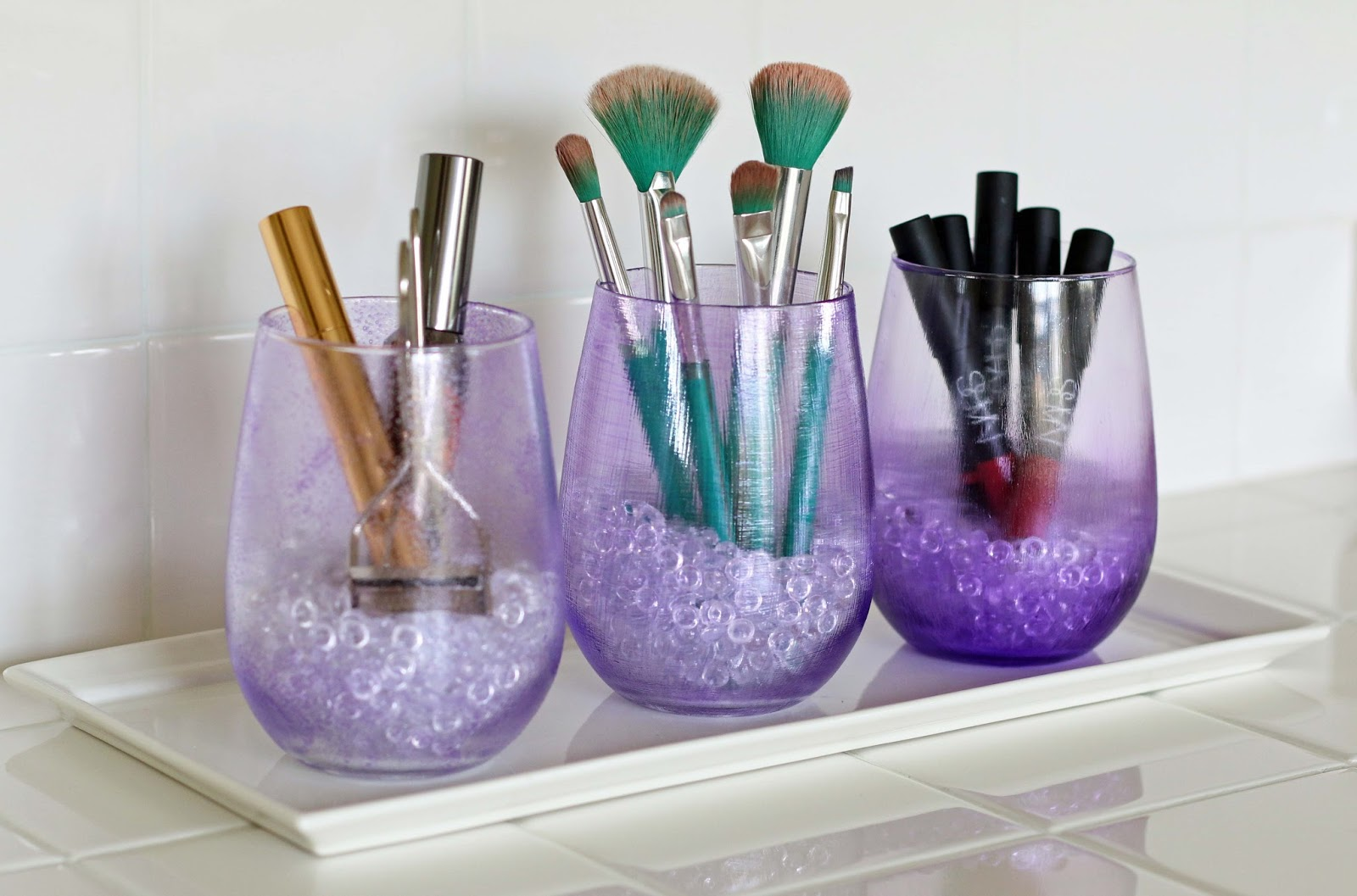 Three Purple Mod Podge glasses are used for makeup storage and organizing.