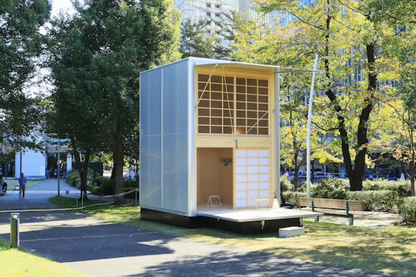 The exterior of a MUJI Aluminum Hut, a minimal Japanese prefab house.