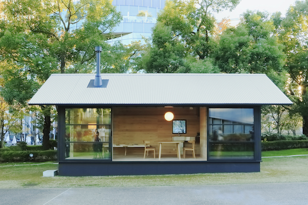 The exterior of a MUJI Wooden Hut, a minimal tiny house in Japan.