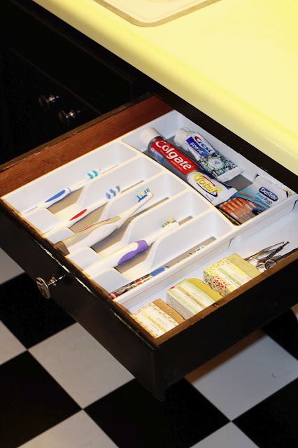 an organizer tray declutters a bathroom sink drawer