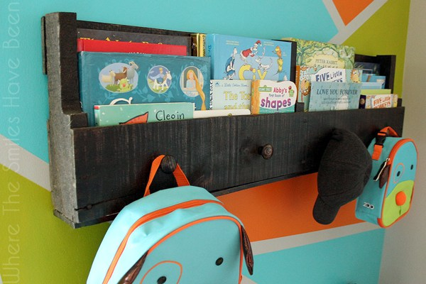 A reclaimed wood pallet bookshelf stores assorted children's books, backpacks, and a baseball hat.
