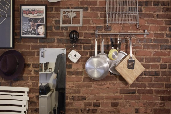 The wall storage rack in Mary Helen Rowell's 90 sq ft West Village micro-apartment.