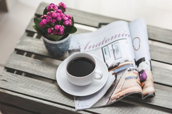 A magazine, a flower in a pot, and a cup of coffee are on top of a wooden crate.