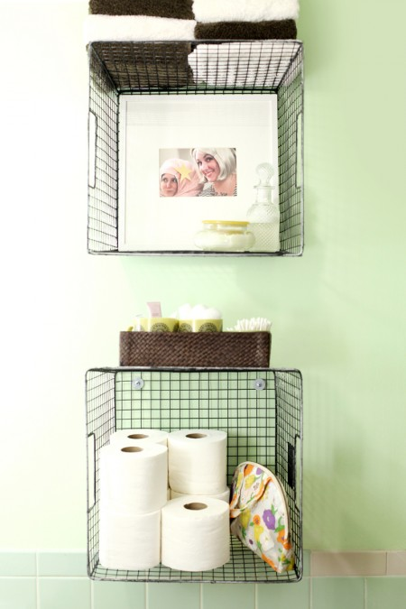 bathroom wall-mounted wire baskets storing toilet paper, toiletries, and towels