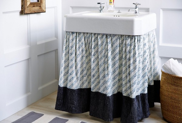 skirted pedestal sink used for hidden storage in a bathroom