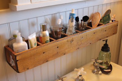 wooden divided box mounted above a sink and storing various bathroom, grooming, and hygiene supplies