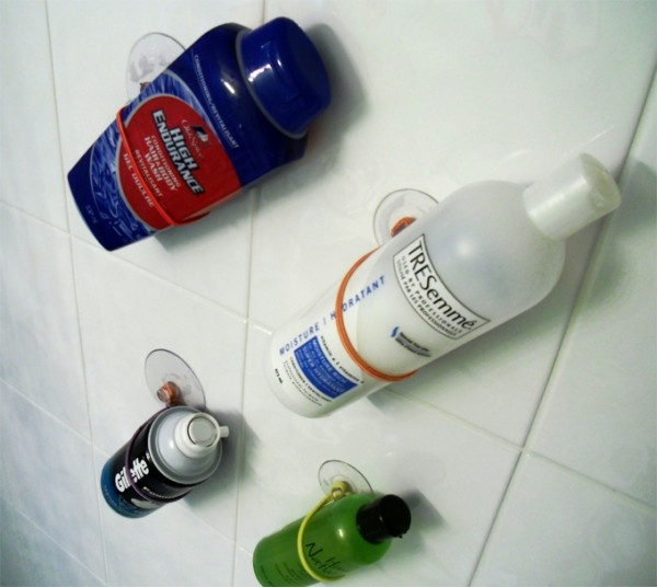 diy shower storage hacks made from suction cups and hair ties are storing body wash, hair products, and gillette shaving cream