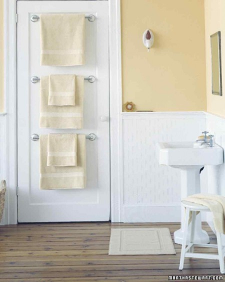 martha stewart's towel bar trio mounted on the back of a bathroom door