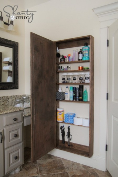 a wooden diy bathroom storage cabinet is storing listerine, rubbing alcohol, nail polish, clorox wipes, curling irons, aveeno lotion, and more