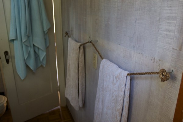 A Space Saving Bathroom Towel Rack Made From Three Eye Bolts And Rope