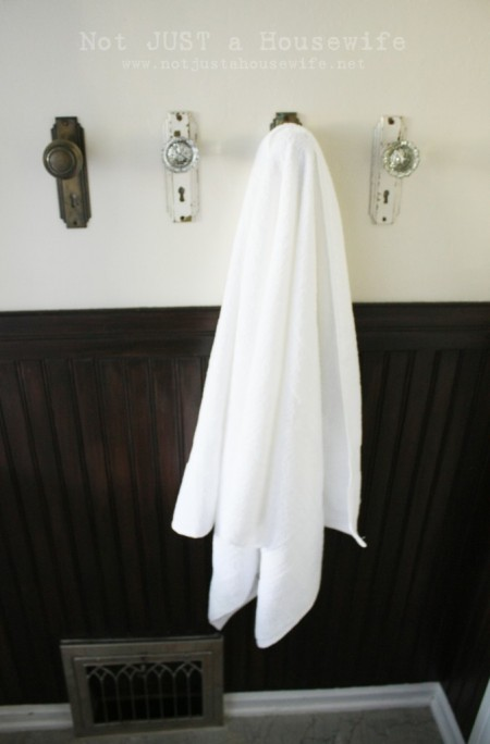 four wall-mounted door knobs, one of which is hanging a white towel