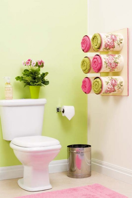 bathroom storage hack: six wall-mounted and decorated tin cans storing six towels