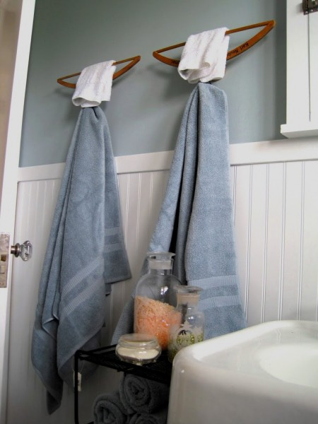 a creative bathroom storage hack is wall-mounted upside down hangers storing two body towels and two face towels
