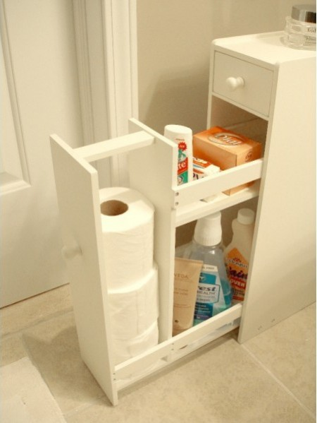 a slim white proman free-standing cabinet is next to a wall and storing various bathroom supplies
