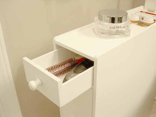 a white proman free-standing cabinet is storing a hair brush and a braun electric razor