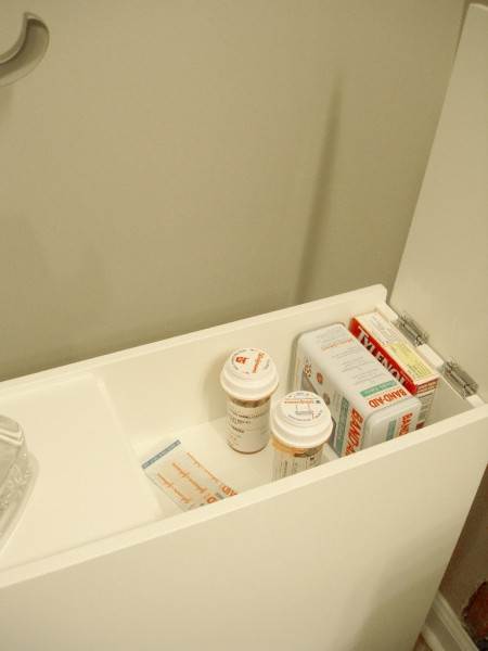 free-standing cabinet's top hidden storage space is storing walgreens prescription bottles, a bandaid can, wrapped bandaids, and a tylenol box